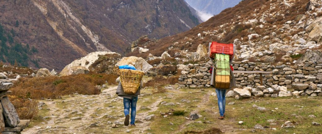 Heavily loaded porters on Nepal hiking trails