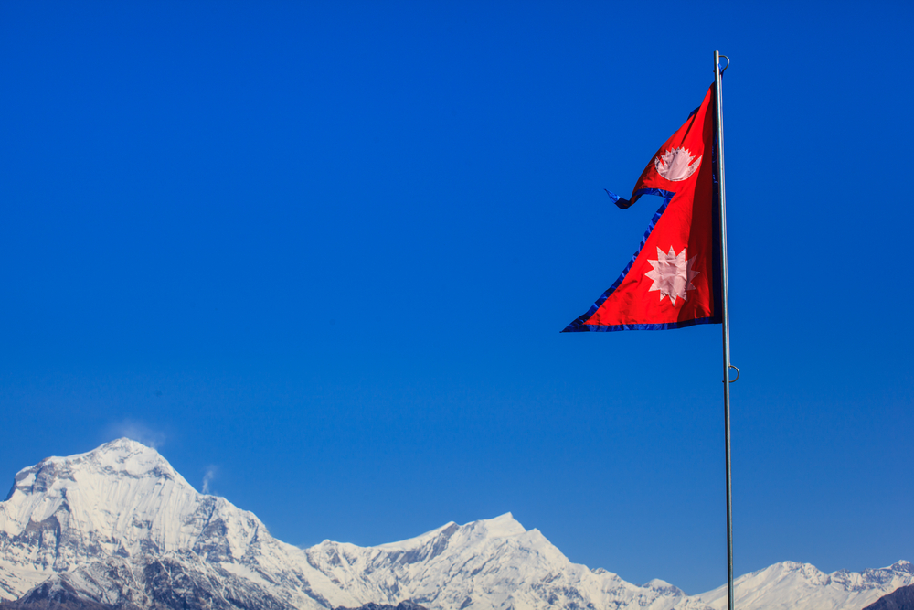 Nepalese flag waving in front of Annapurnas